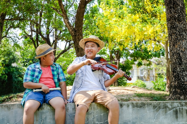 Happy, two boys smiling and laughing, playing music, violins and flutes at the backyard