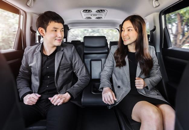 車の後部座席に座って幸せな2つのビジネスの男性と女性