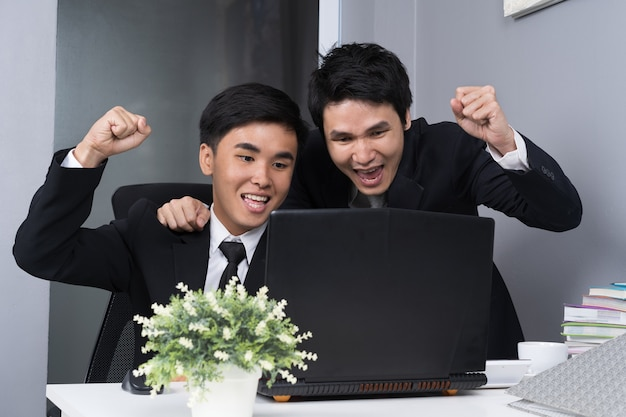 Happy two business man using laptop to  successful working project