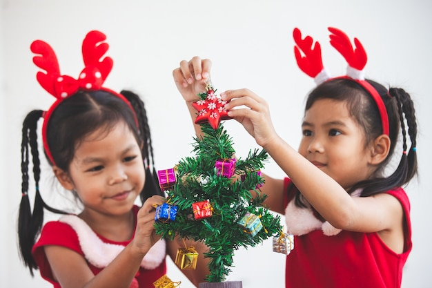Happy two cute asian child girls decorating christmas tree for celebrating christmas
