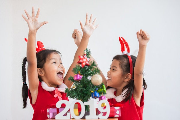 Happy two cute asian child girls with numbers 2019 and christmas tree