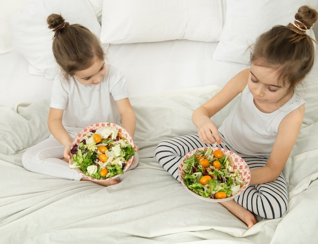 Счастливые двое милых детей едят овощной салат в спальне на кровати. здоровое питание для детей и подростков.