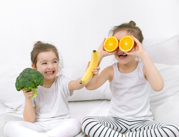Два счастливых милых ребенка играют с фруктами и овощами на светлом фоне. здоровое питание для детей.