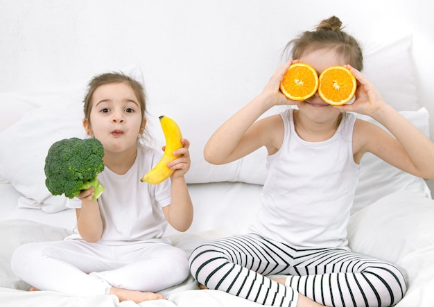 Happy two cute children play with fruits and vegetables on light.