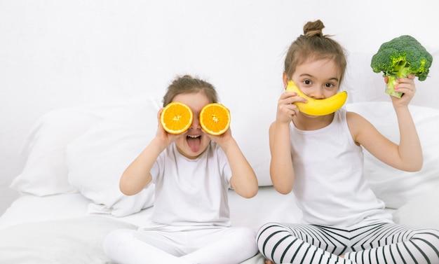 Счастливые две милые дети играют с фруктами и овощами.