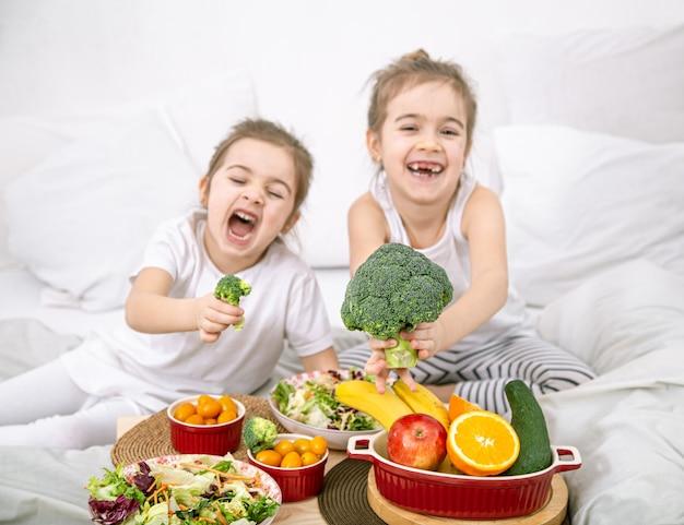 Счастливые две милые девушки едят фрукты и овощи в спальне на кровати. здоровое питание для детей и подростков.