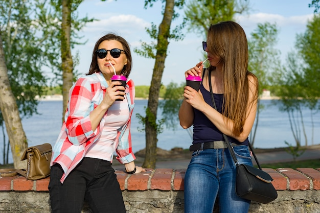 Happy two female friends drinking coffee