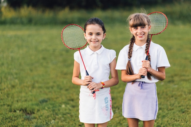 Happy two female friends holding badminton in hand