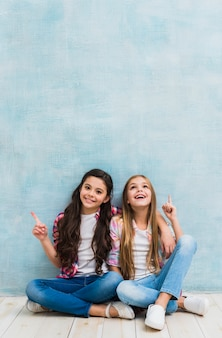 Happy two girls sitting in front of blue wall pointing their finger upward