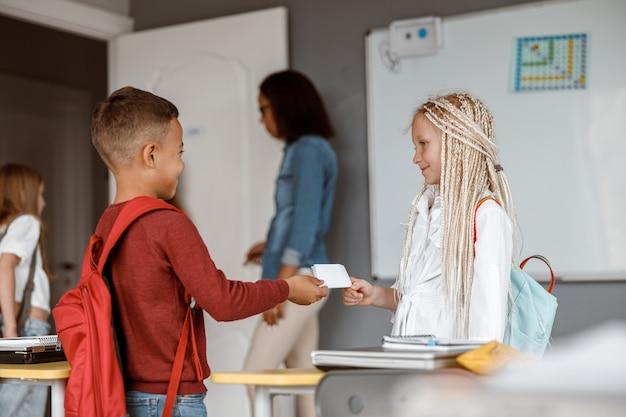 교실에 서 있는 배낭을 메고 행복한 두 아이
