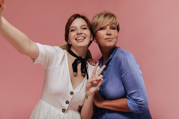 Счастливые две дамы с короткими волосами в современных летних платьях показывают знак мира, улыбаются и делают селфи на розовом фоне.