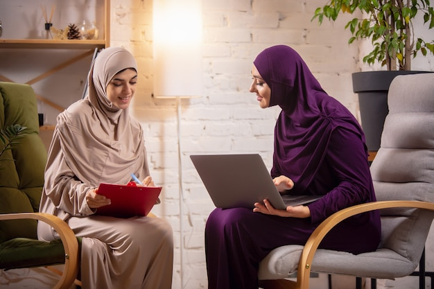 Happy two muslim women at home during lesson, studying near computer, online education