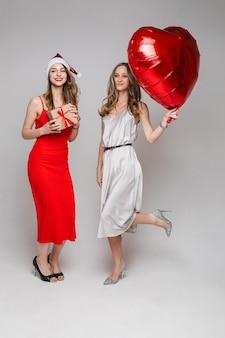 Счастливые две красивые женщины с воздушным шаром в форме сердца и подарочной коробкой позируют, изолированные на серой стене