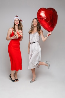 Happy two pretty women with heart-shaped balloon and gift box posing in studio, on grey.