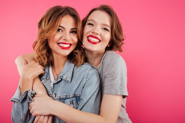Happy two women friends hugging.