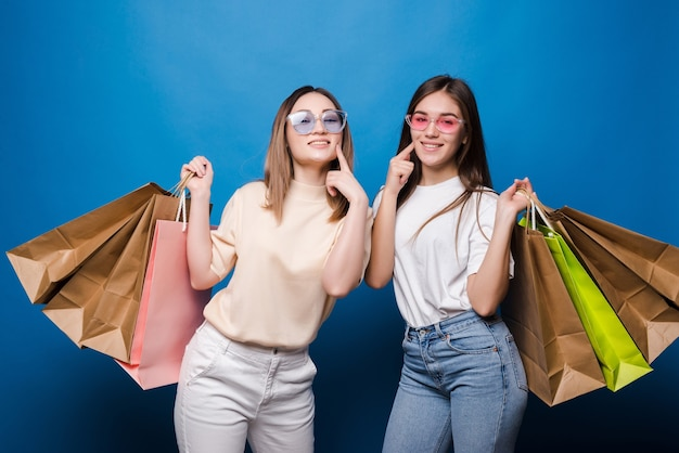 Happy two women with colorful shopping bags on blue wall