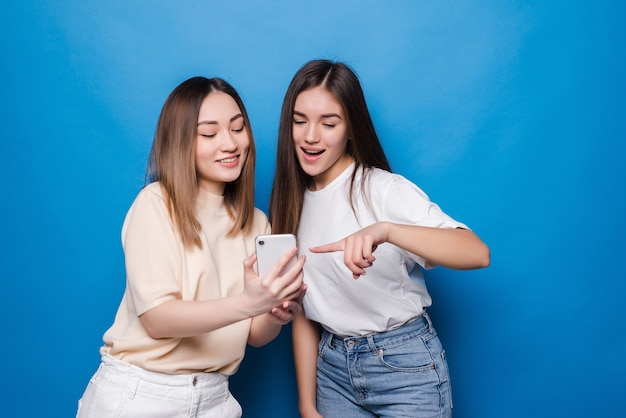 Happy two young girls laughing and pointing finger at screen of smartphone while taking selfie isolated over blue wall