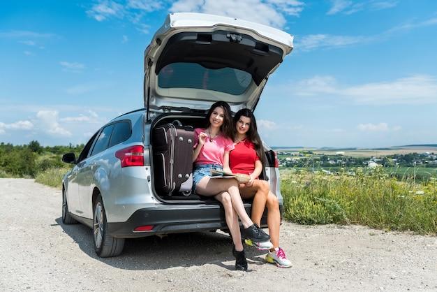 자동차 여행으로 여행 행복 두 젊은 여자. 여행 및 휴가 개념