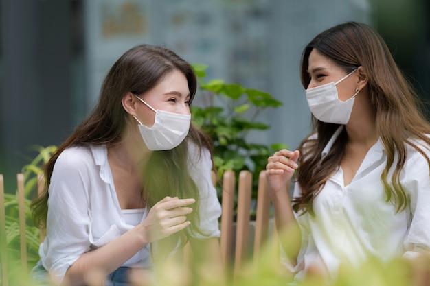 Счастливые две молодые женщины со смайликом в защитной маске разговаривают и смеются