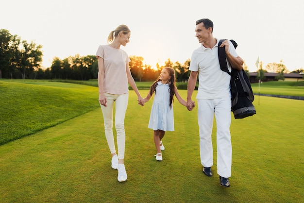 Happy united family of golfers walks after game.
