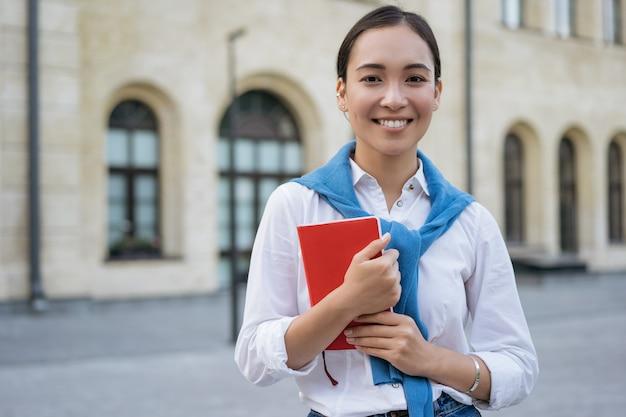 本を持って、大学に歩いて幸せな大学生。教育の概念