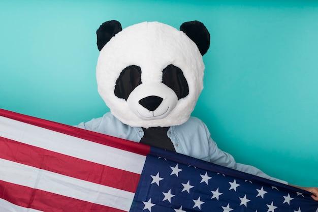 파란색 벽에 서있는 동안 미국 국기를 들고 행복 인식 할 수없는 남자