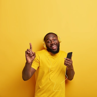 Happy unshaven black man drags to rhythm of music, listens popular song in headphones, connected to smart phone, enjoys playlist, raises hands, dressed in casual t shirt in one tone with wall
