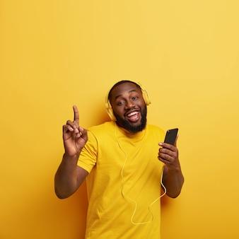 Счастливый небритый темнокожий мужчина тащит в ритме музыки, слушает популярную песню в наушниках, подключен к смартфону, наслаждается плейлистом, поднимает руки, одет в повседневную футболку в тон со стеной