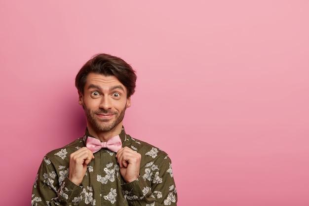 Felice l'uomo con la barba lunga si aggiusta il papillon, indossa una camicia alla moda con stampa floreale, si prepara per il primo appuntamento