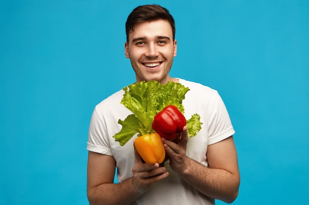 Happy unshaven young guy vegan with muscular fit body with broad radiant smile carrying fresh colorful veggies and lettuce from grocery shop. veganism, raw food and dieting
