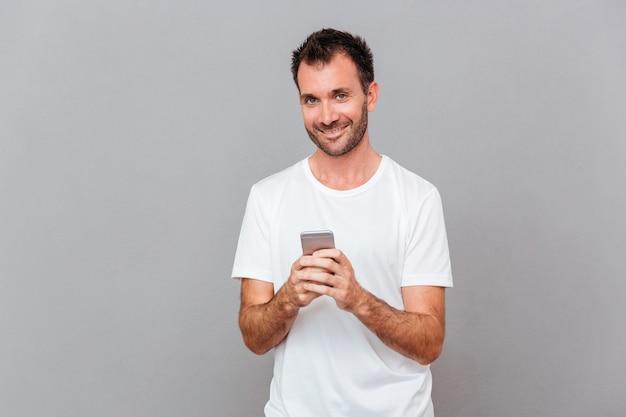 スマートフォンを持って灰色の背景の上のカメラを見て幸せなuoung男