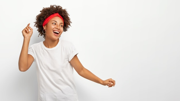 Happy upbeat woman raises arms, looks away with delighted expression, dressed in casual wear