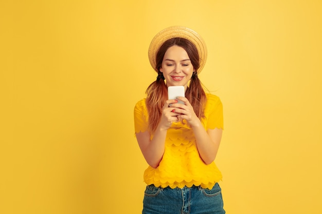 Happy using smartphone. caucasian woman's portrait on yellow studio background. beautiful female model in hat. concept of human emotions, facial expression, sales, ad. summertime, travel, resort.