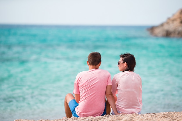 Happy vacation couple relaxing on white sand and pristine turquoise water on beach in greece.