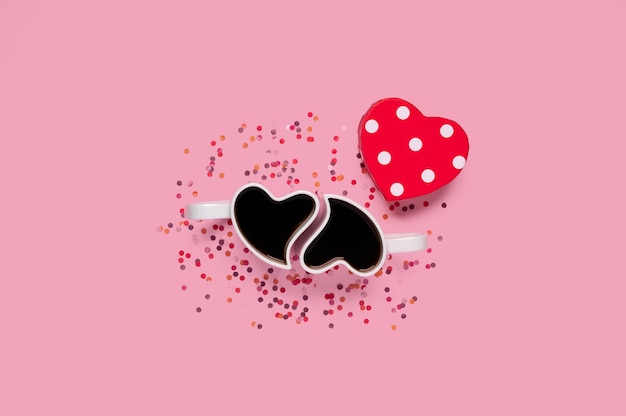 С днем святого валентина. чашки кофе с подарочной коробкой в форме сердца с конфетти на розовом
