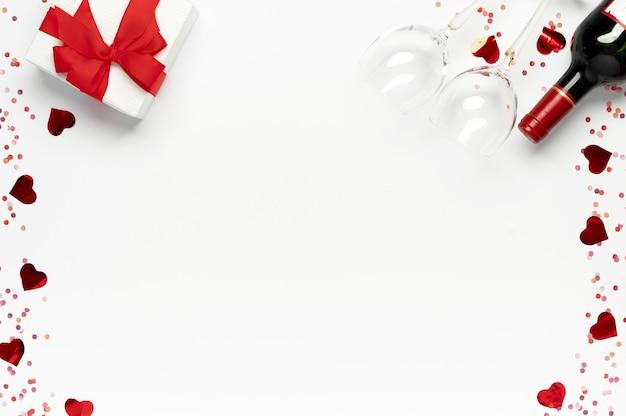 ハッピーバレンタインデー。ギフトボックス、ワインボトル、白い背景に紙吹雪とグラスと赤いバラの束