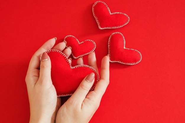 Счастливого дня валентина. вид сверху на руки женщины, держащей сердце из фетра ручной работы над красным