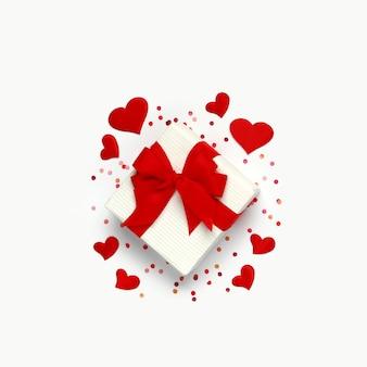 ハッピーバレンタインデー。白い背景に小さなハートと紙吹雪がたくさんあるギフトボックス。
