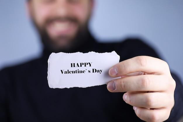 해피 발렌타인 데이 그의 손에 작은 흰색 종이 조각