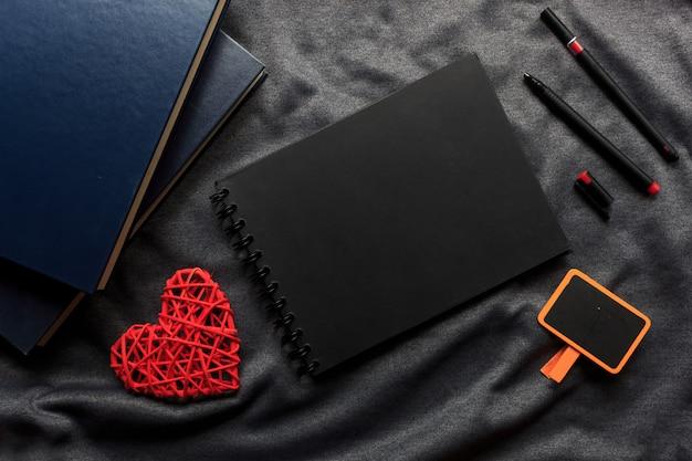 해피 발렌타인 데이 개념, 검은 책, 붉은 심장 및 회색 천으로 펜 프리미엄 사진