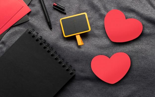 해피 발렌타인 데이 개념, 검은 책, 붉은 심장 및 회색 천으로 펜