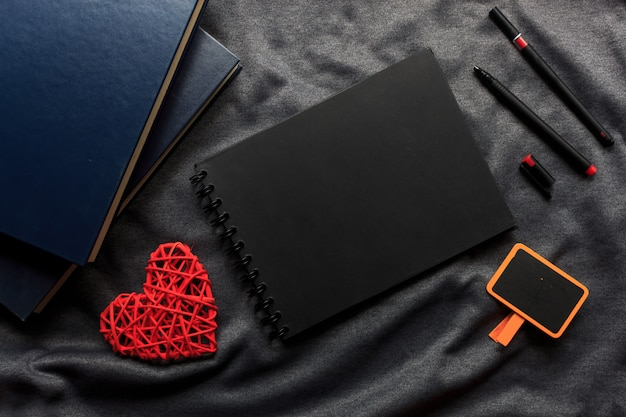 Happy valentine's day concept, black book, red heart and pen on gray cloth