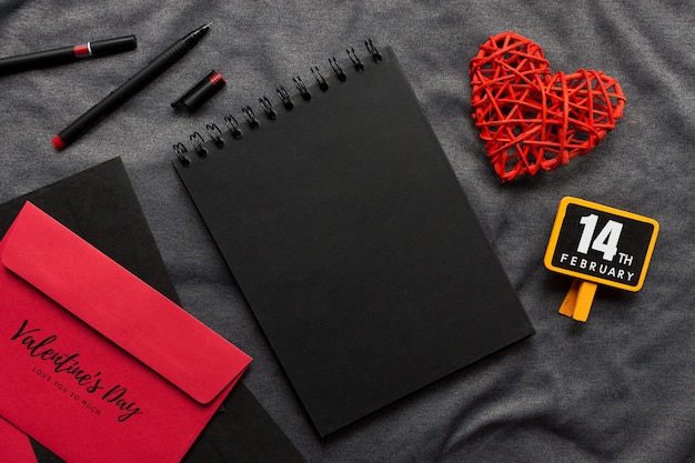Happy valentine's day concept, black book, red heart and pen on gray cloth Premium Photo