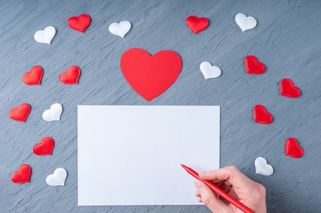 Happy valentine's day greetings. hand holds a red pen to write a love letter or congratulation on a gray background