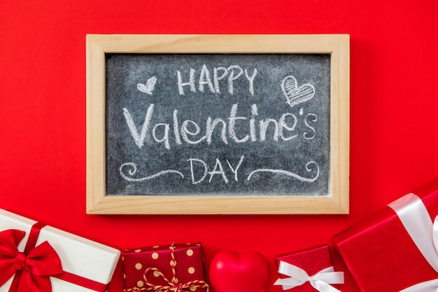 Happy valentine's day handwritten text on blackboard with gift box