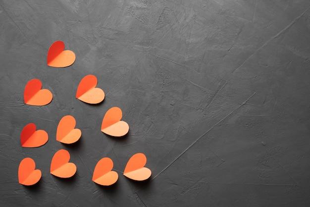 幸せなバレンタインデー。暗いコンクリートの背景に赤い紙で作られたハート。バレンタインデーのコンセプト。バナー。スペースをコピーします。