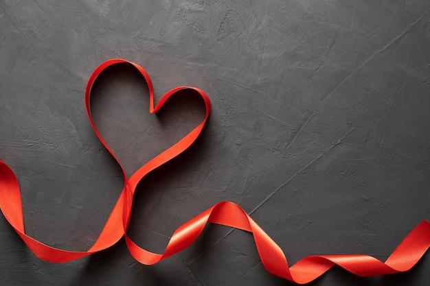 幸せなバレンタインデー。暗いコンクリートの背景に赤いリボンのハート。バレンタインデーのコンセプト。バナー。スペースをコピーします。