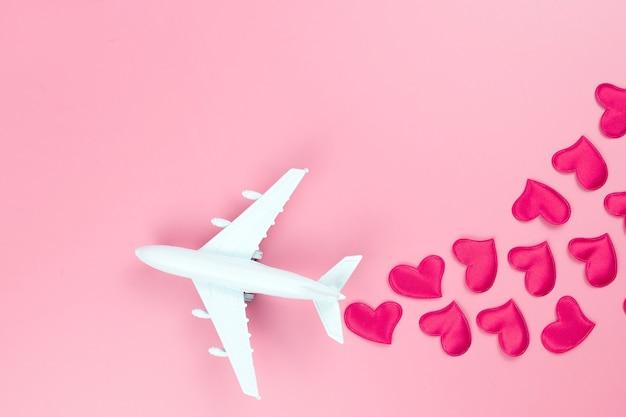 幸せなバレンタインデー。ピンクの背景におもちゃの飛行機と赤いハート