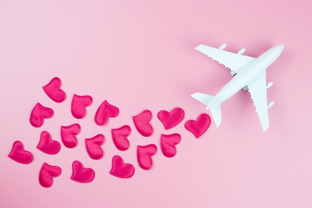 Happy valentine's day. toy plane and red hearts, on a pink background