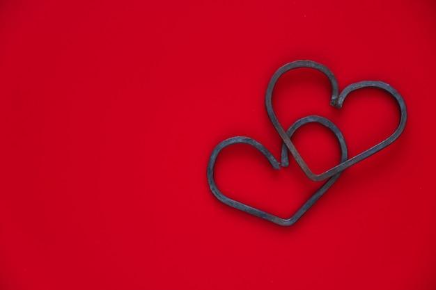 幸せなバレンタインの日。赤い背景に2つの鍛造金属ハート。フラットレイ、コピースペース。